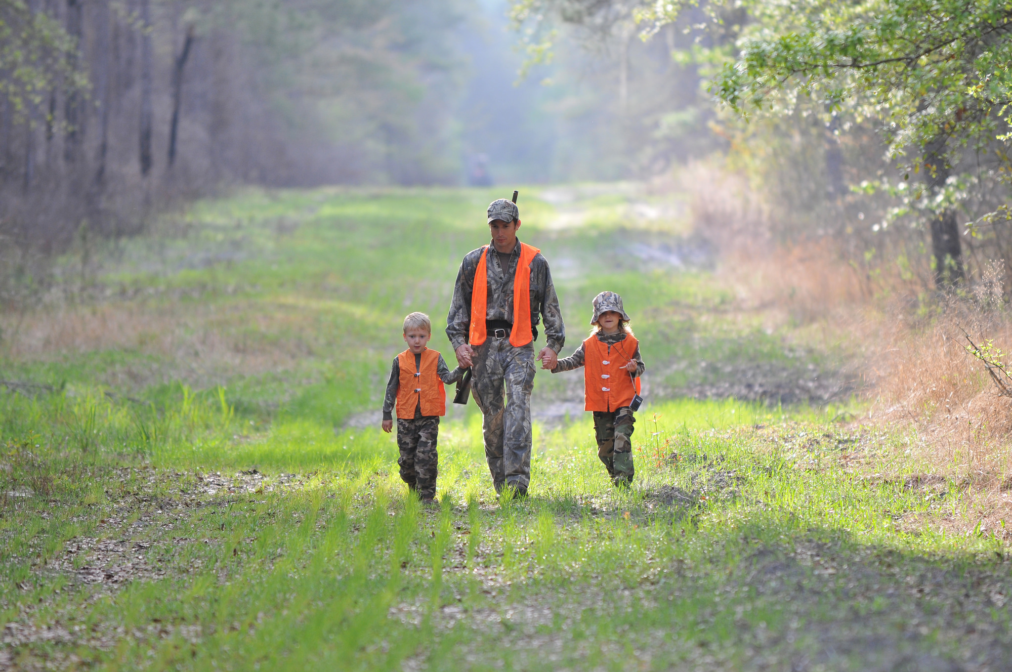 NFA Gun Trust - person walking through grass in a forest, with two children