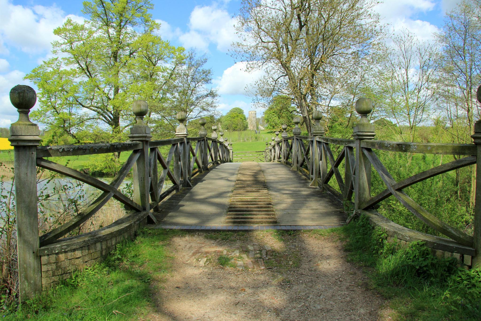 wood and stone bridge with trees and greenery around