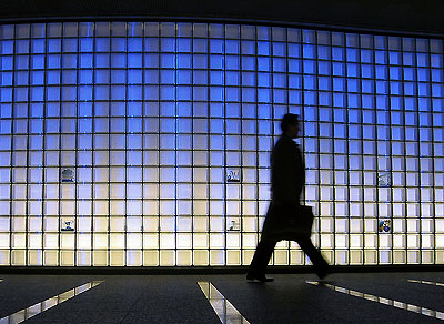 LLC, estate planning, law - silhouette of person walking in front of a fully-lit wall