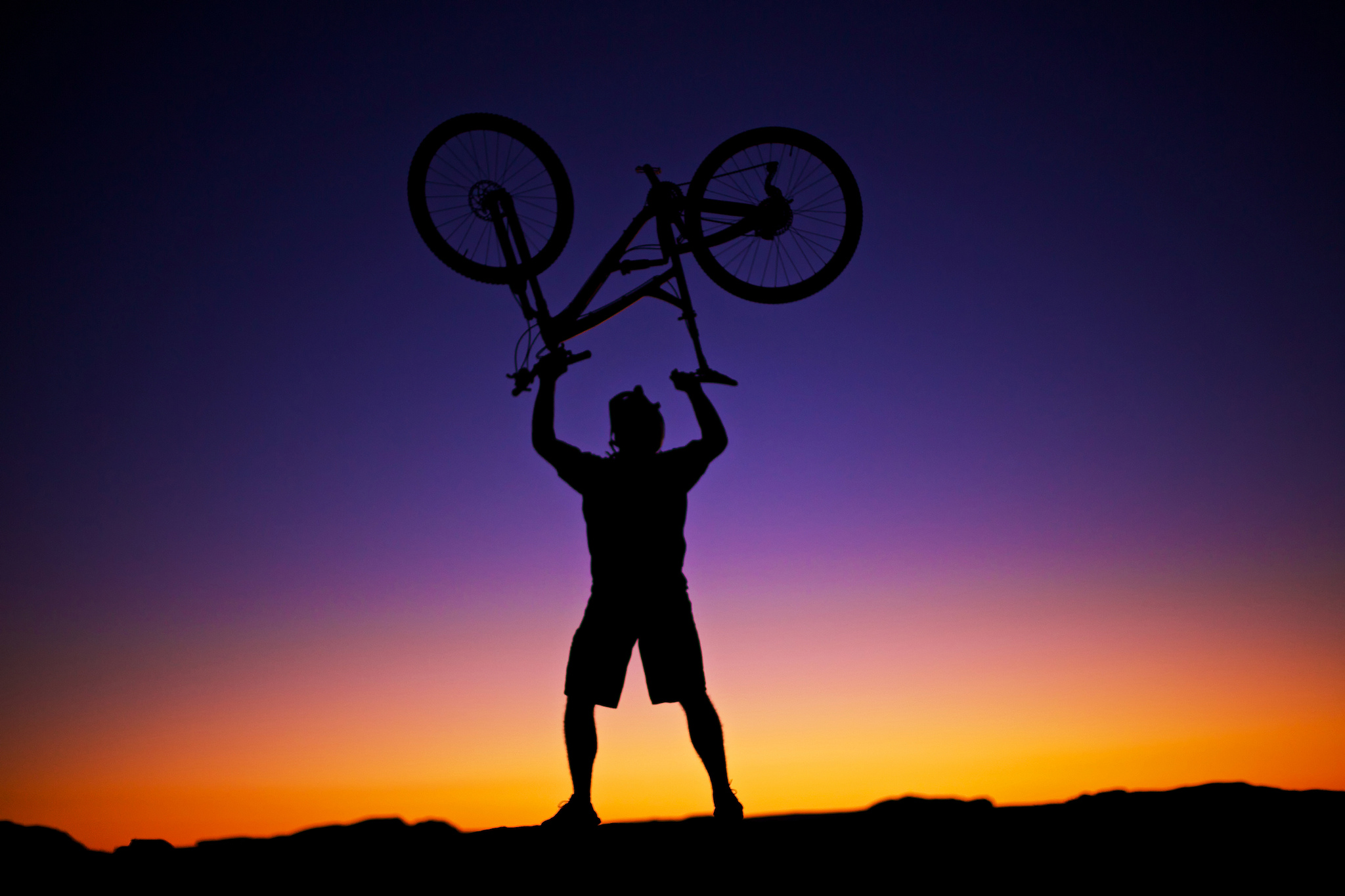 mountain biking, law - silhouette of person holding bicycle upside down over head