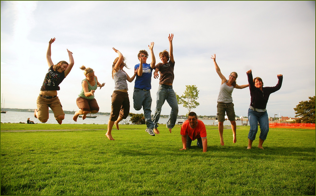 group of people mid-air jumping on grass