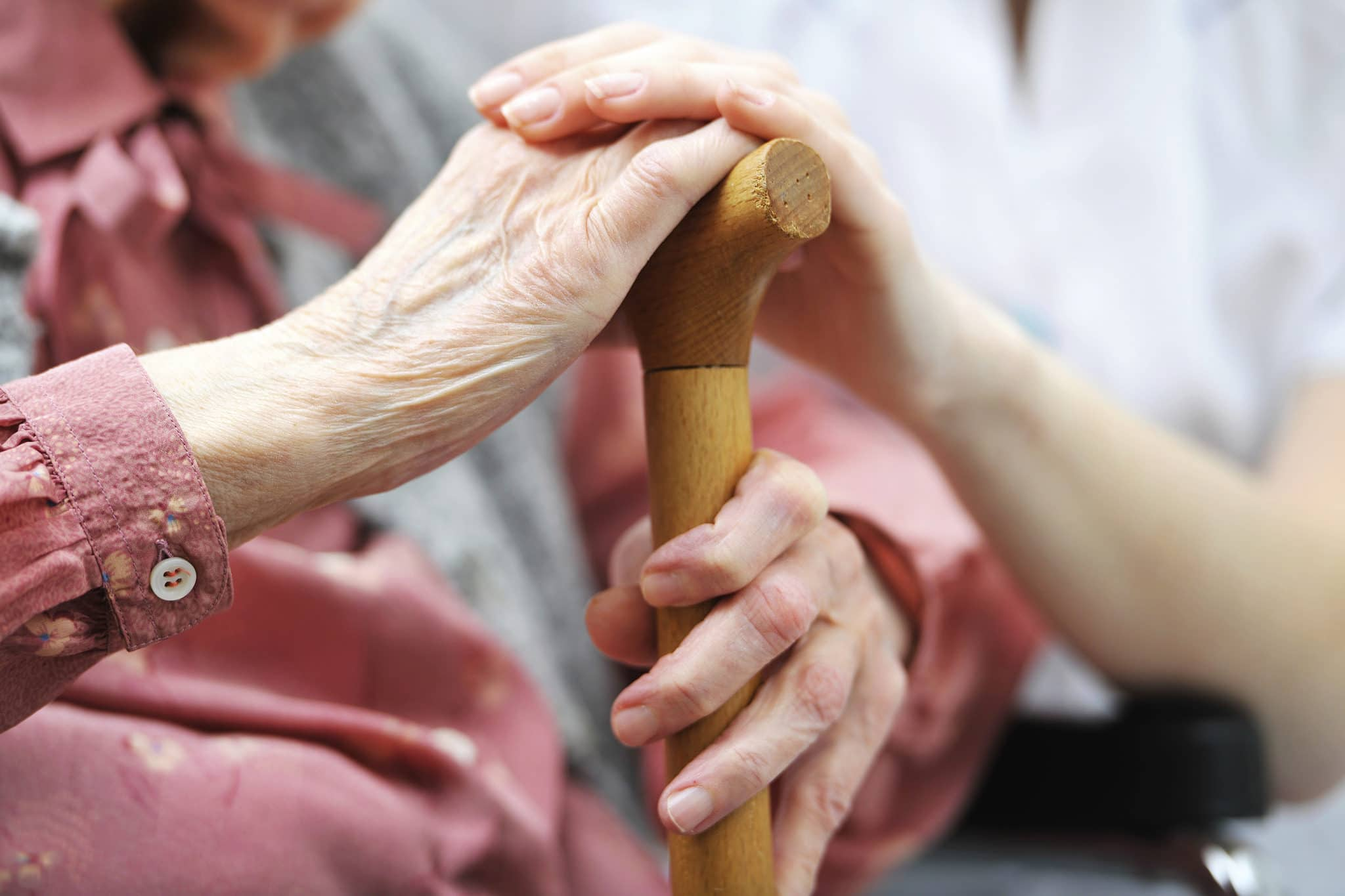 elder care - two hands holding a walking stick