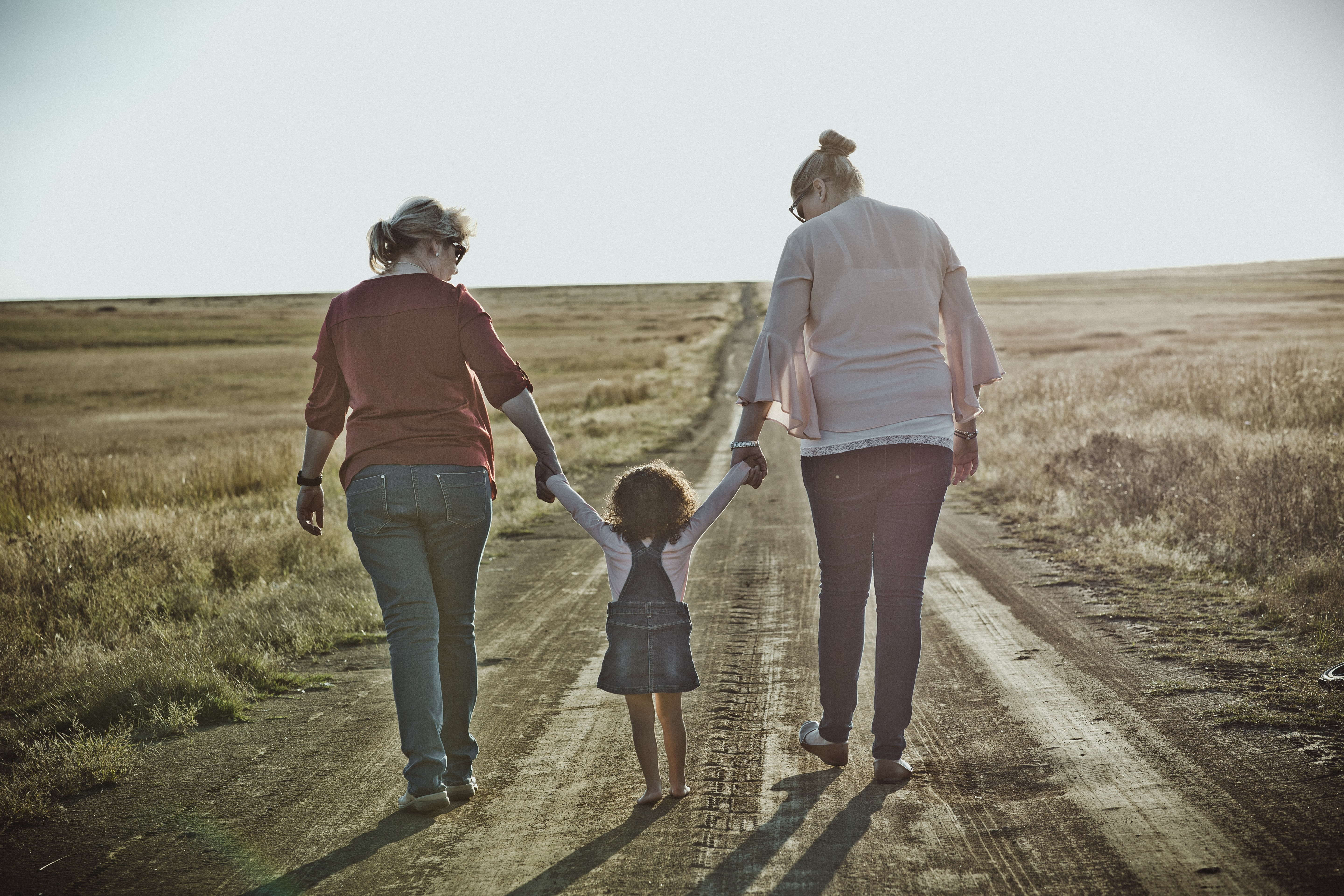 estate planning attorneys - two adults holding a child, on a dirt road