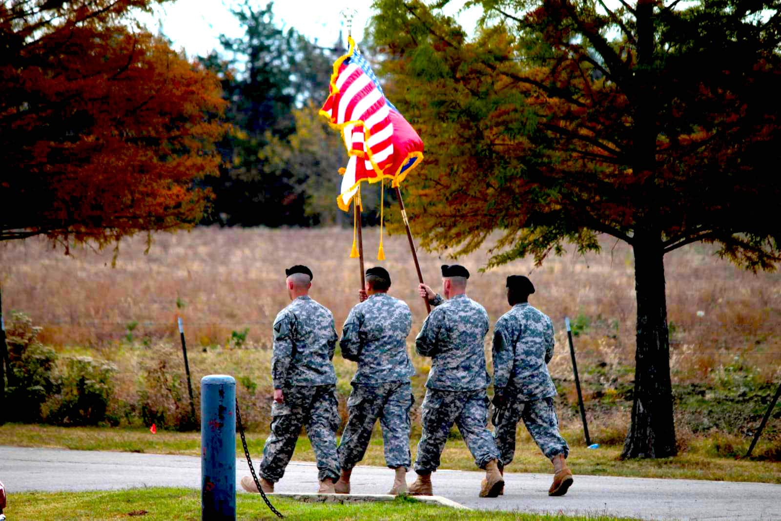 elder care attorneys - four people in uniform walking holding the American flag