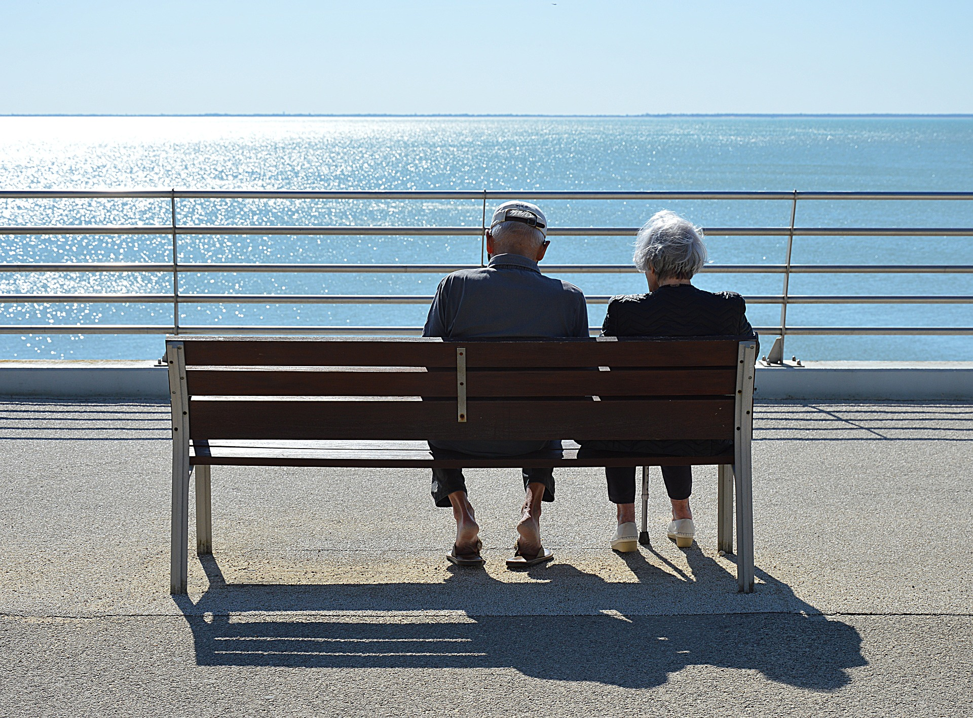 long-term care needs - two people sitting on a bench, looking out over the water
