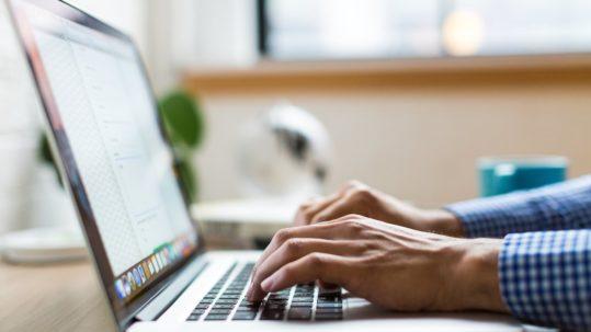 online trust - hands typing on laptop keyboard