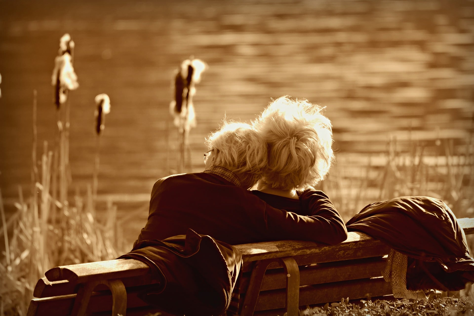 Medicaid vs Long Term Care Insurance - two people sitting on a bench looking out across water